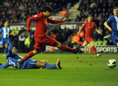 Liverpool's Luis Suarez scores his hat-trick and the fourth goal of the game for his side against Wigan.