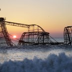 The sun rises in Seaside Heights, New Jersey, behind the Jet Star Roller Coaster which has been sitting in the ocean after part of the Funtown Pier was destroyed during Superstorm Sandy. The private owners of the amusement pier that collapsed in Seaside Heightsare working with insurers to devise a plan to dismantle the ride and get it out of the ocean. (AP Photo/Mel Evans)